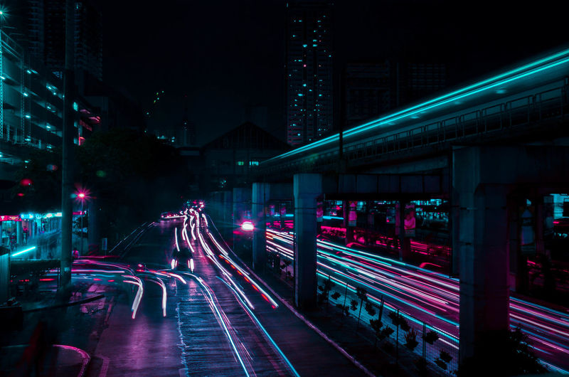 Light trails on road by bridge at night