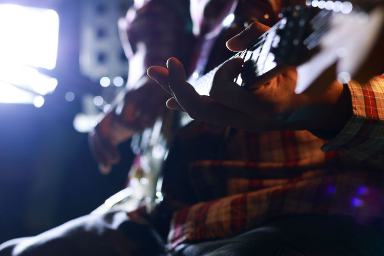 Close-up midsection of man playing guitar in music concert