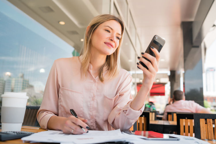 Young woman using smart phone on table