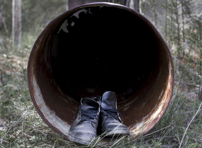 Low section of person wearing shoes on land