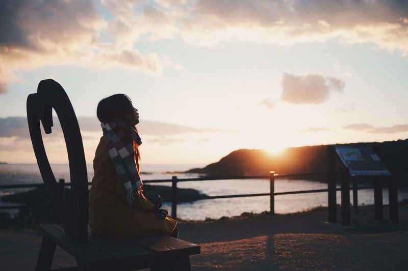 Woman sitting by sea against sky during sunset