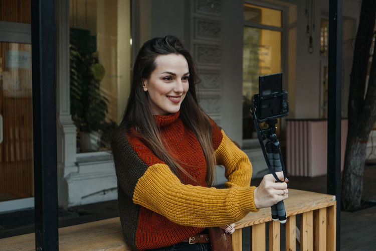 Smiling woman vlogging while standing outdoors