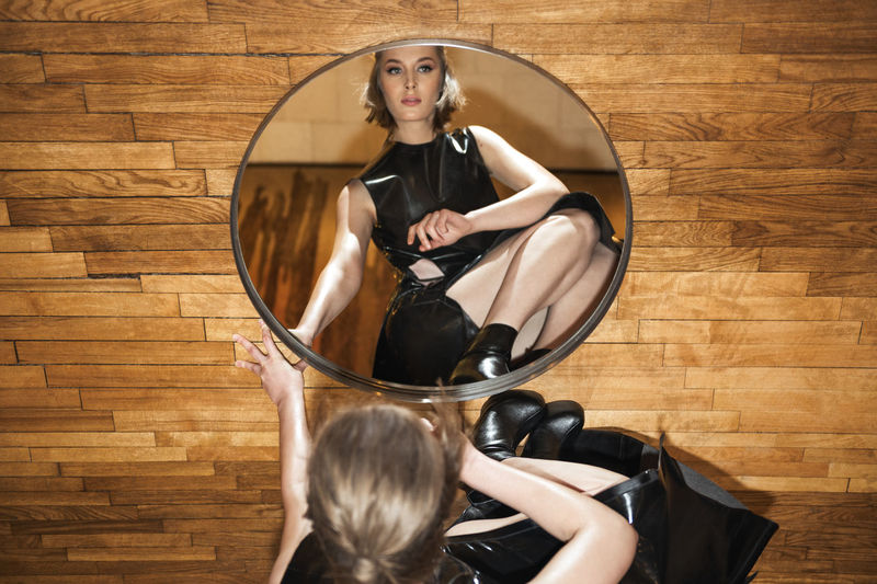 Beautiful woman with her reflection in mirror sitting on hardwood floor