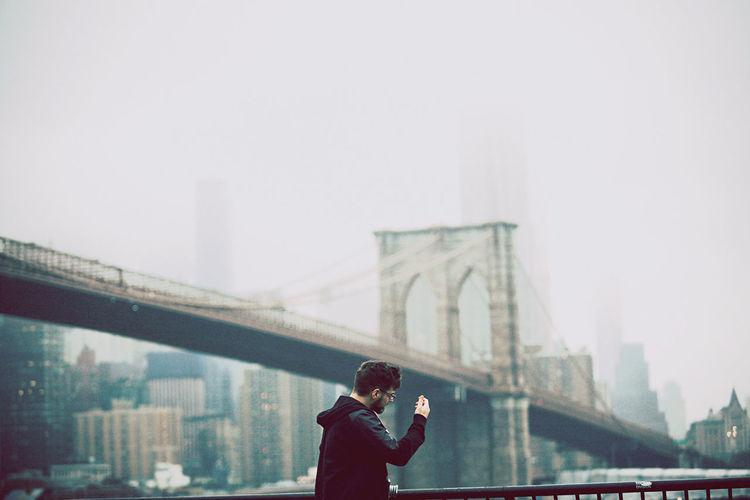 Man on bridge against sky in city