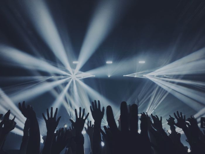 People with arms raised at concert