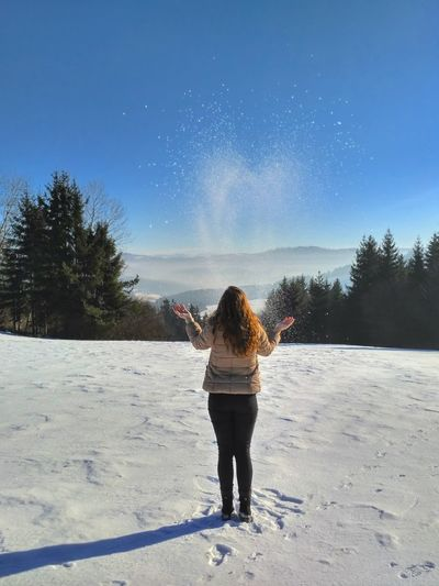 Rear view of woman walking in snow against clear sky