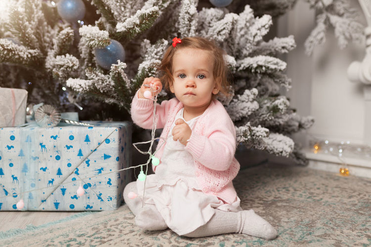 Portrait Of Cute Baby Girl Sitting By Christmas Tree At Home
