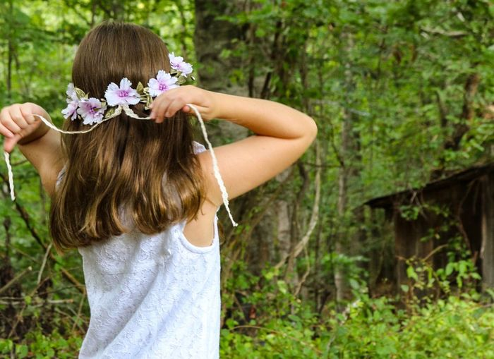 Rear view of girl wearing flowers against trees