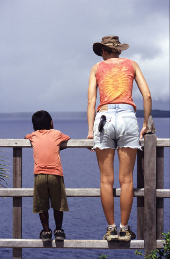 Rear view of woman and boy standing by sea against sky