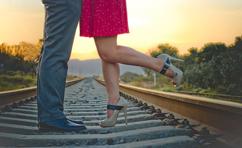 Low Section Of Couple Standing On Railroad Track