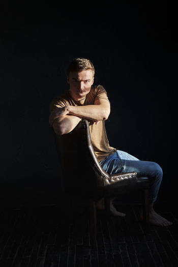 Portrait of man sitting on chair against black background