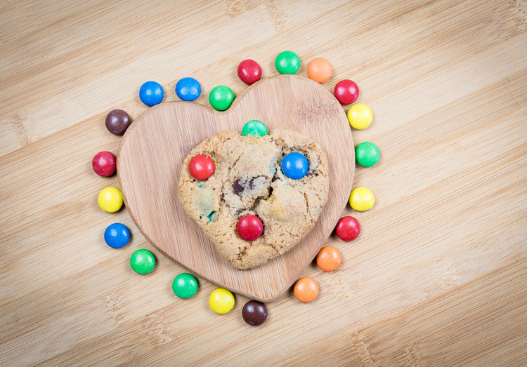 Directly above view of fresh cookie on heart shape serving board amidst colorful candies over wooden table