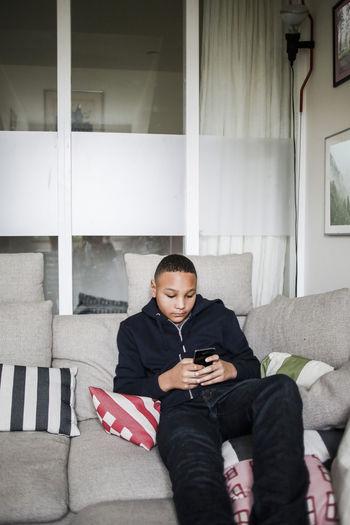 Full length of a boy using mobile phone