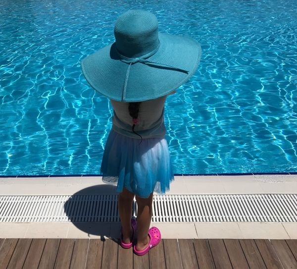 Rear View Of Girl Wearing Blue Hat Standing At Poolside On Sunny Day
