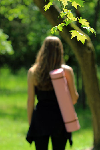 Yoga in the park Background Blond Hair Carrying Bag Concept Copy Space Day Female Fitness Green Healthy Lifestyle Nature One Person Outdoors Park People Real People Rear View Relaxation Summer Sunshine Tranquility Trees Well Being Yoga Yoga Mat