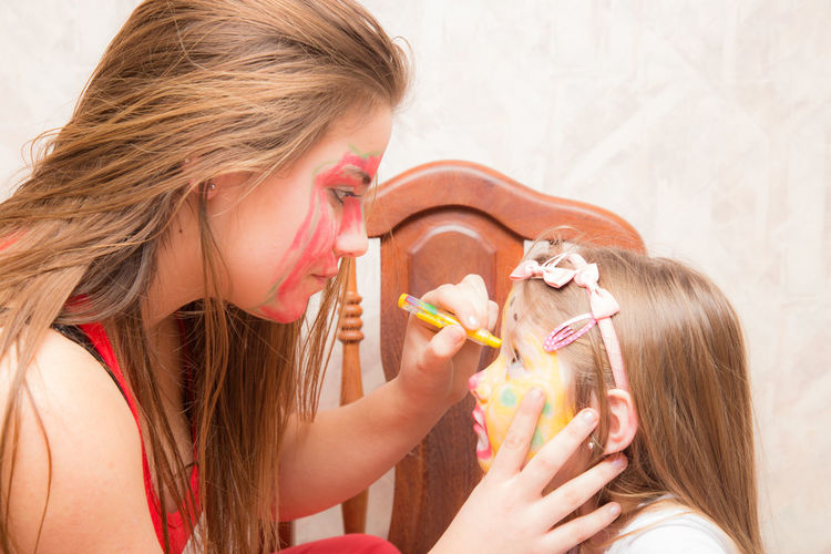Face Painting Adult Blond Hair Body Painting Bubble Wand Child Childhood Close-up Day Face Paint Face Painted Child Girls Headshot Holding Human Body Part Human Hand Indoors  Long Hair People Real People Togetherness Two People Young Adult Visual Creativity