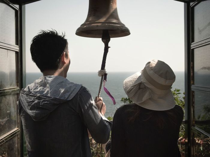 Rear View Of Couple Ringing Bell