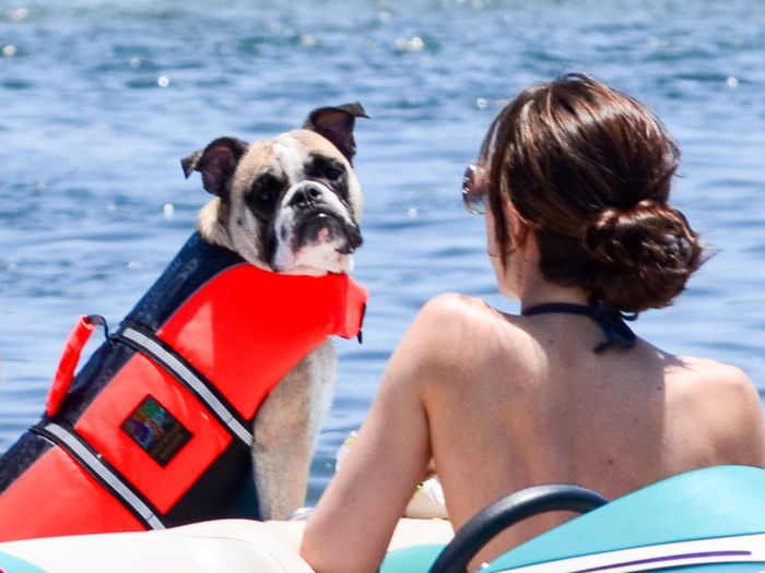 Woman with dog in boat against lake during sunny day