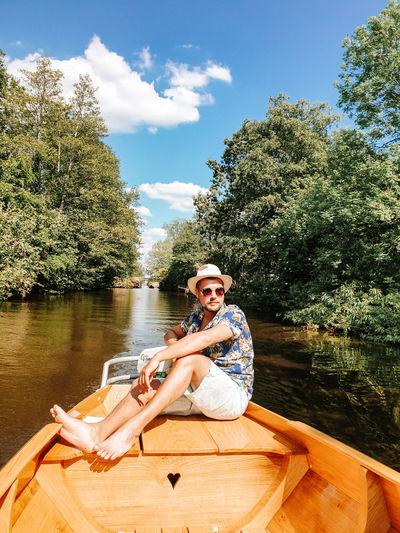 Smiling man sitting on boat in lake