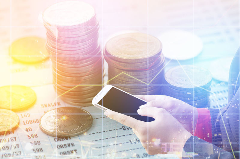 Digital composite image of hands holding using mobile phone with graphs and coins desk