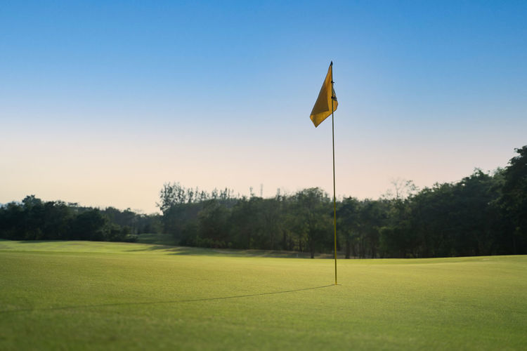Scenic view of golf course against clear sky