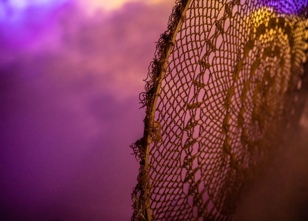 CLOSE-UP OF FISHING NET ON WALL
