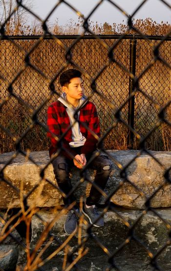 Thoughtful teenage boy looking away while sitting on retaining wall seen through chainlink fence