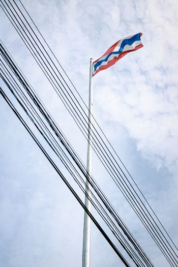 Low angle view of flag and cables against sky