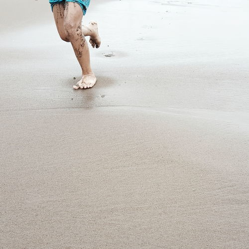 Low Section Of Boy Running On Wet Sand At Beach