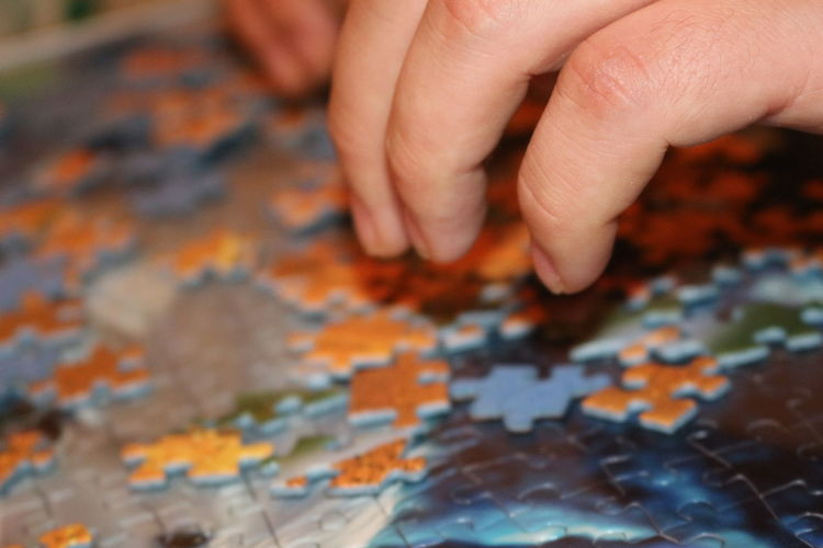 Cropped Image Of Hands Solving Jigsaw Puzzle