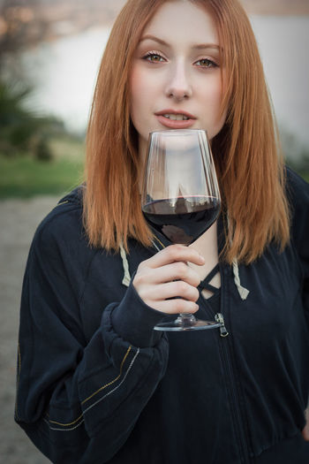 Portrait of young woman holding red wine in glass