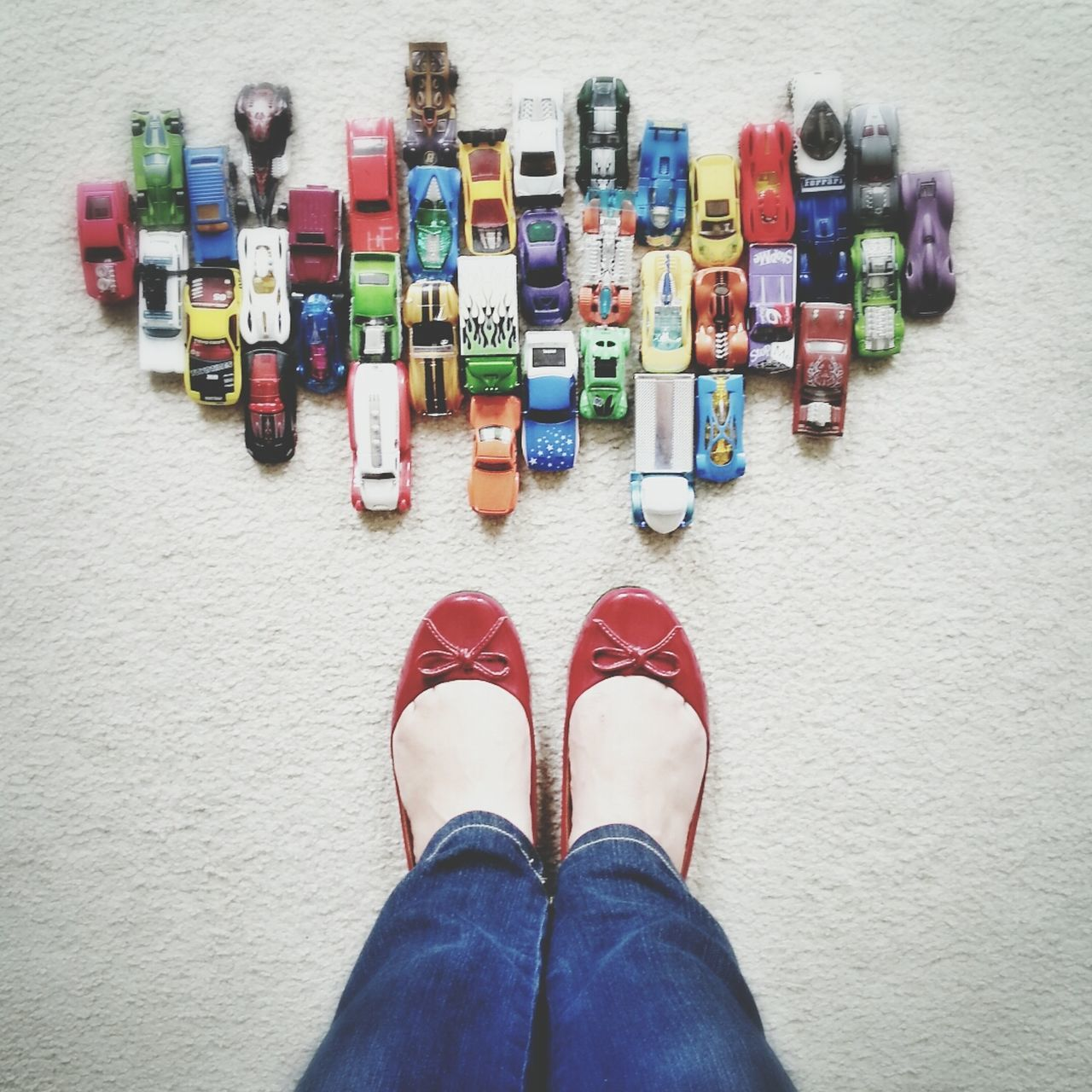 Low section of girl with toy cars on floor