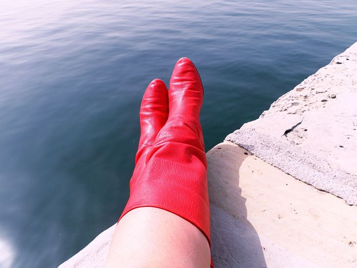 Low section of woman in red boots