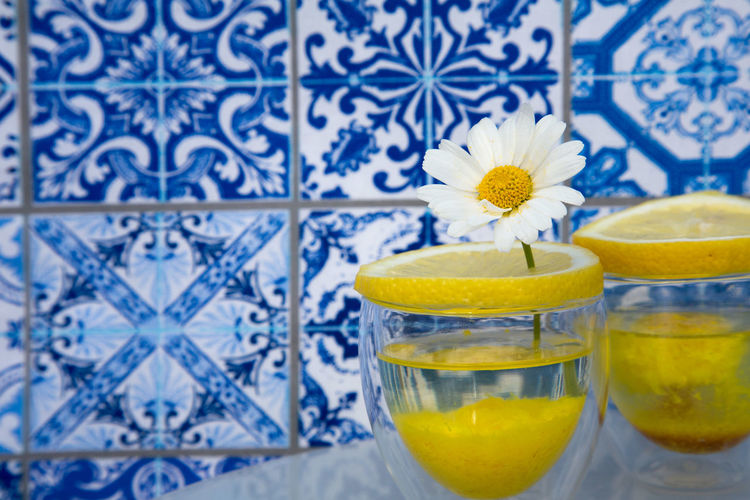 Daisy Stuck In Fruit Slice On Glass Against Blue Tiled Wall