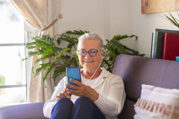 Smiling senior woman video calling while sitting at home
