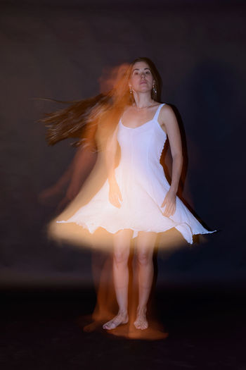 Beautiful young woman dancing at night