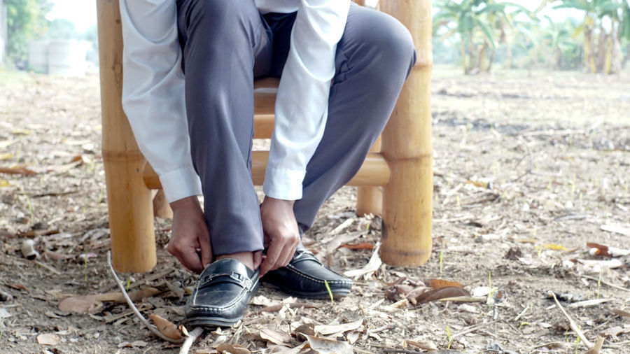 Low section of man wearing shoes while sitting on land