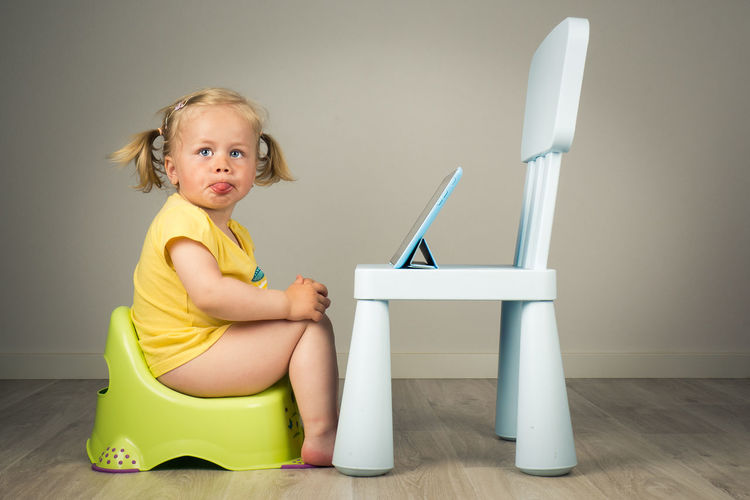 Portrait of young girl sitting on potty with tablet