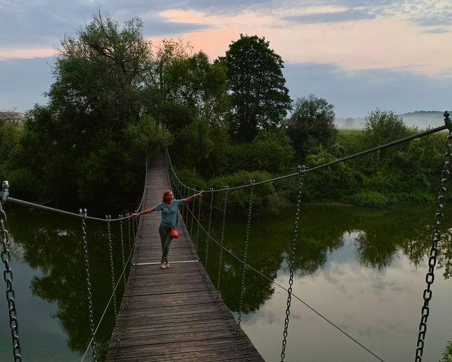 People on footbridge against sky
