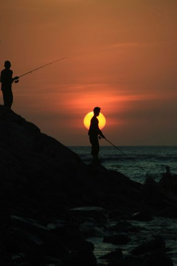 Silhouette man fishing in sea against sunset sky