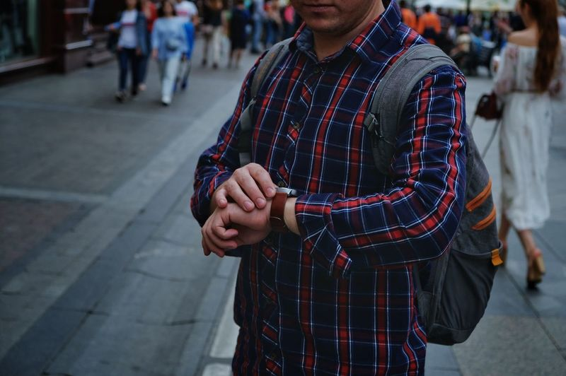 Midsection Of Man Checking Time While Standing On Street In City