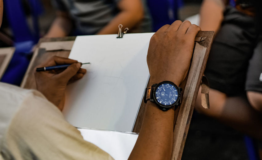 Cropped image of man sketching on paper