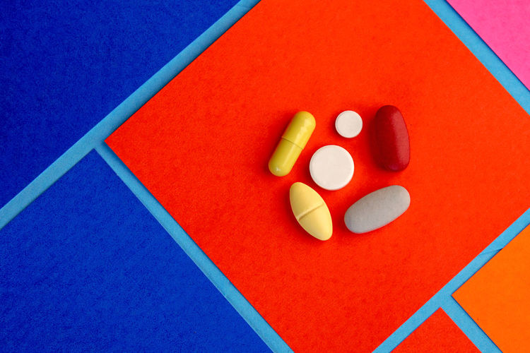 High angle view of colorful pills on paper