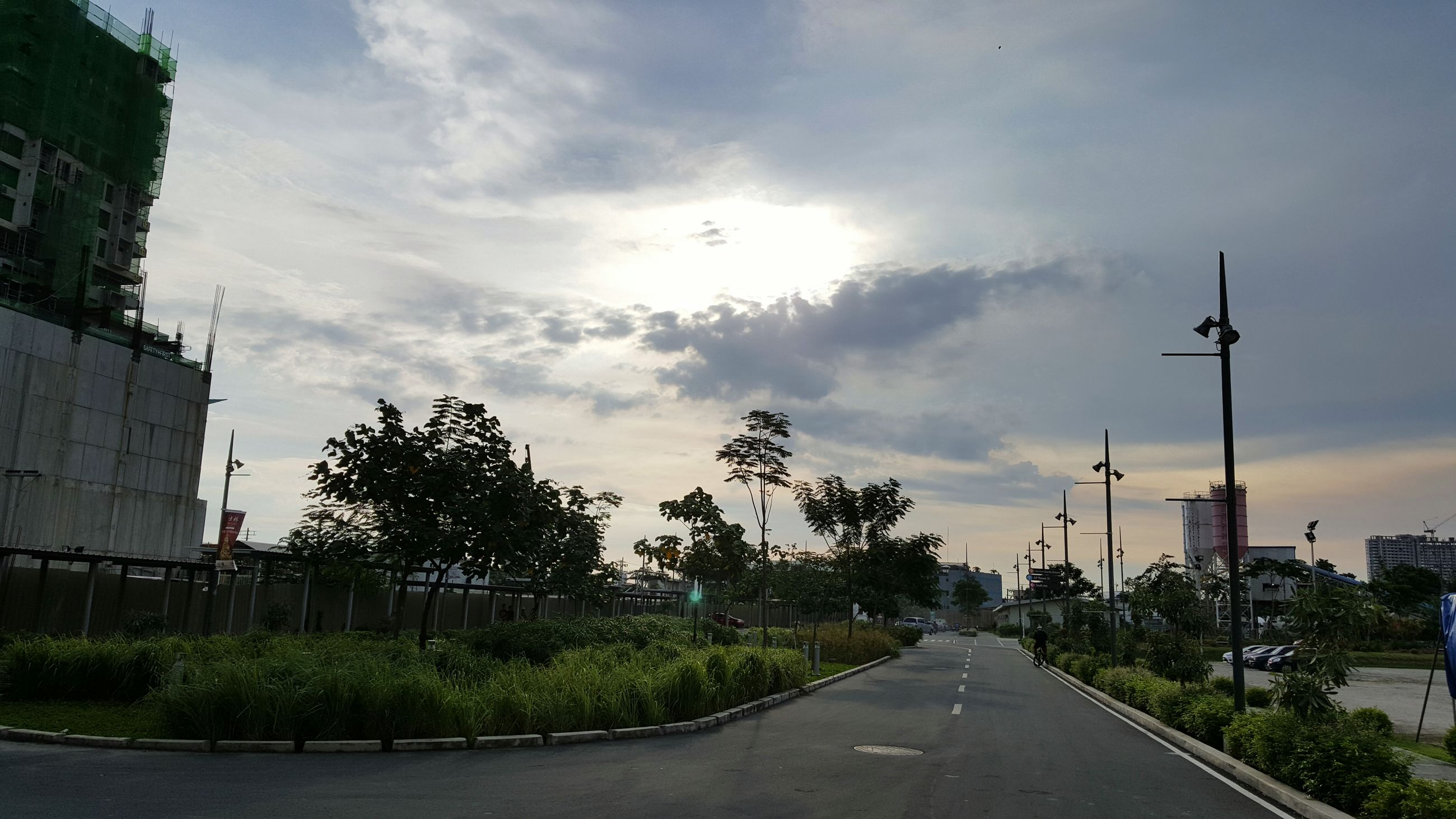 road, the way forward, cloud, empty, transportation, long, sky, tree, solitude, street, architecture, tower, surface level, building exterior, diminishing perspective, plant, outdoors, narrow, day, tall - high, vanishing point, remote, countryside, empty road, tranquility, tranquil scene, cloudy, tall