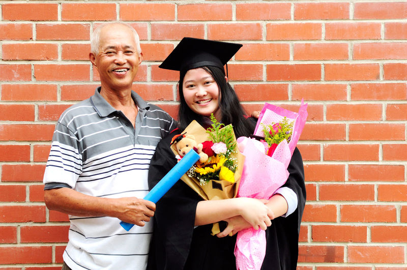 Portrait of father and daughter standing against brick wall during convocation