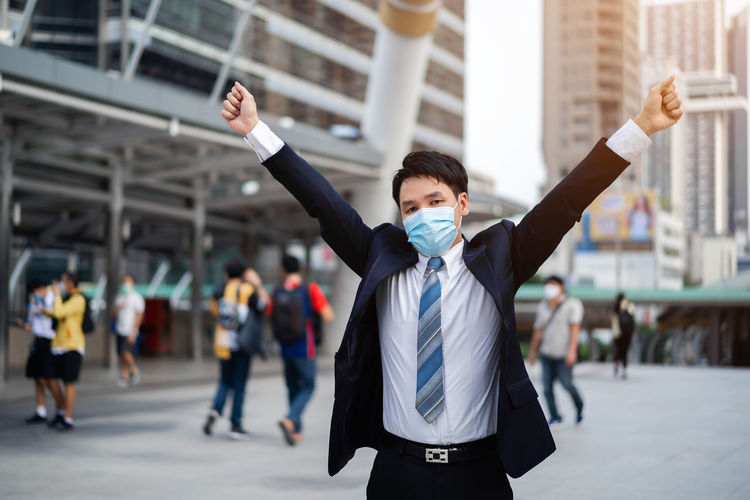 Businessman wearing mask standing against building on street