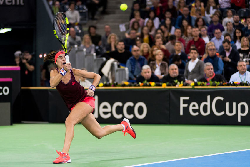 CLUJ NAPOCA, ROMANIA - FEBRUARY 10, 2018: Romanian tennis player Sorana Cirstea playing tennis against Carol Zhao during a Fed Cup match between Romania and Canada Arena Fed Cup Romania Sorana Cirstea Stadium Tennis Tennis Ball WTA Woman Action Concentration Crowd Crowded Hard Court Hitting People Player Playing Tennis Powerful Single Sportswear Tennis Racket Tennis Woman Tenniscourt Tribune