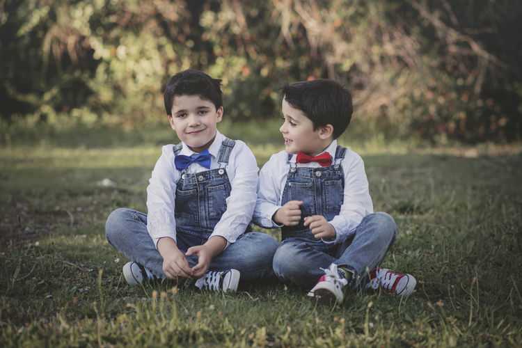 Cute boys sitting on grassy land in park