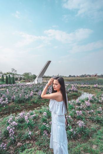 Woman standing by flower field against sky