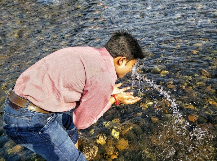 High Angle View Of Man Splashing Water On Face
